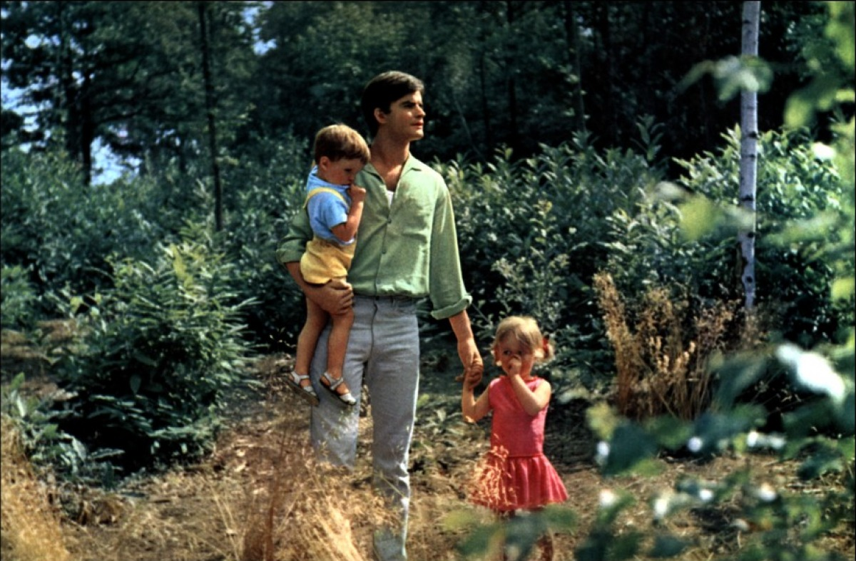 Francoise, wearing a pale green shirt and white slacks, looks for his wife in the forest. He is holding his son, a toddler dressed in a blue top and yellow dungarees, and holding his daughter's hand, who wears a pink dress and sucks her thumb.